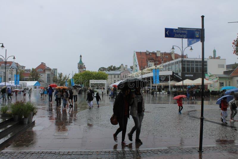 Promenade in Sopot Polen met mensen die onder paraplu's in de regen lopen stock foto's