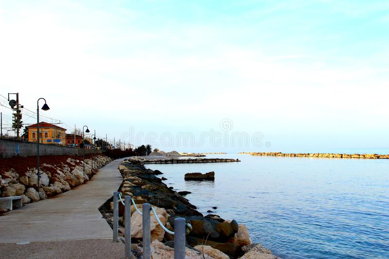 Promenade zwischen Eisenbahnlinien und adriatischen dem Meer umgeben durch Felsen lizenzfreie stockbilder
