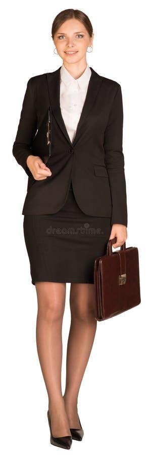 Promenades de femme d'affaires tenant la serviette et le papier photographie stock