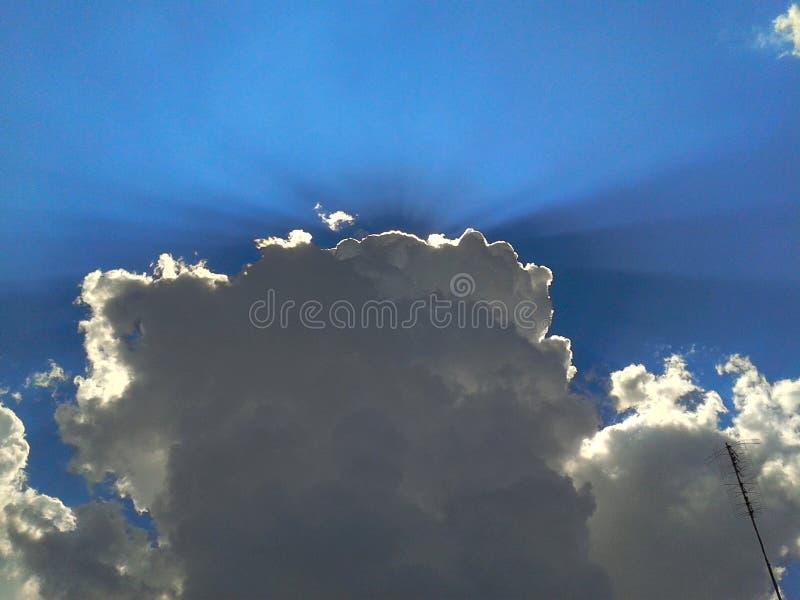 Promienie słońca łamanie przez ciemnych chmur na niebieskiego nieba tle zdjęcie royalty free