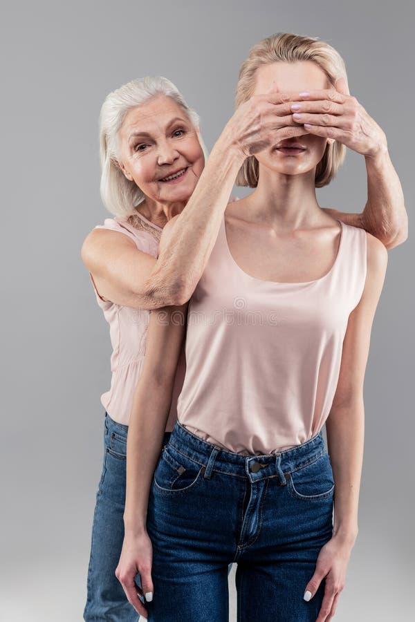 Promieniejąca siwowłosa stara kobieta zadawala podczas gdy zamykający ono przygląda się fotografia stock