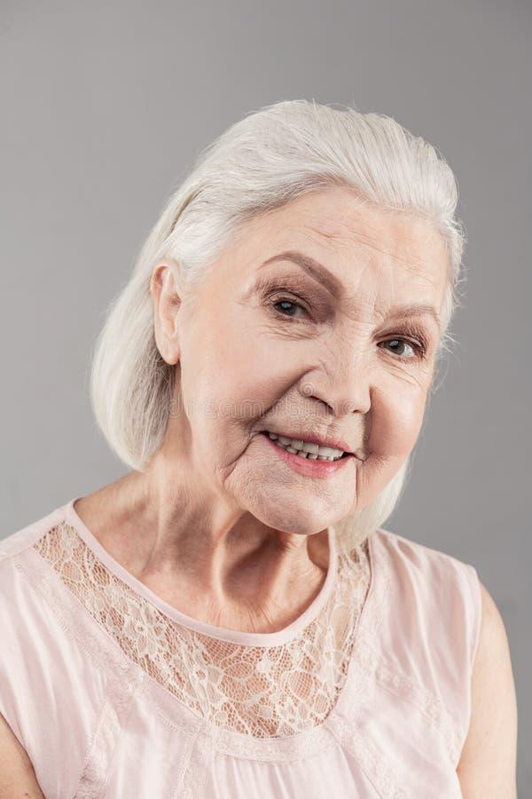 Promieniejąca stara kobieta z krótkiego włosy działaniem jak modela w studiu zdjęcie stock