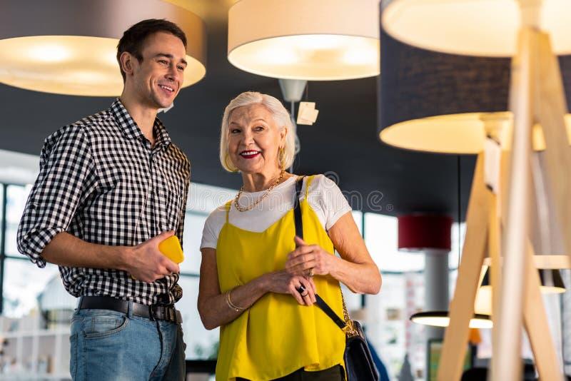 Promieniejąca wspaniała starsza dama dyskutuje lampy kupuje z młodym kawalerem zdjęcie stock