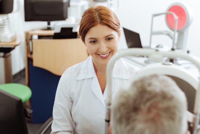 Promieniejąca oko lekarka siedzi blisko laptopu obsługuje podczas gdy ordynacyjny fotografia stock