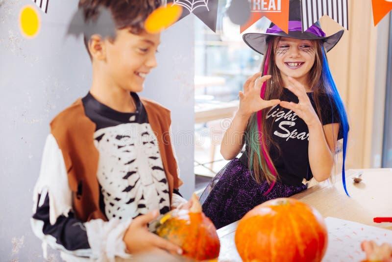 Promieniejąca uśmiechnięta dziewczyna jest ubranym czarownika Halloweenowego kostium uczęszcza śmiesznego przyjęcia obraz stock