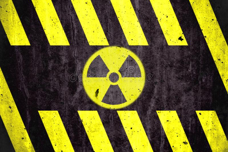 Promieniotwórczy jonizacyjnego napromieniania niebezpieczeństwa symbol z koloru żółtego i czerni lampasami malował na masywnej be zdjęcia royalty free