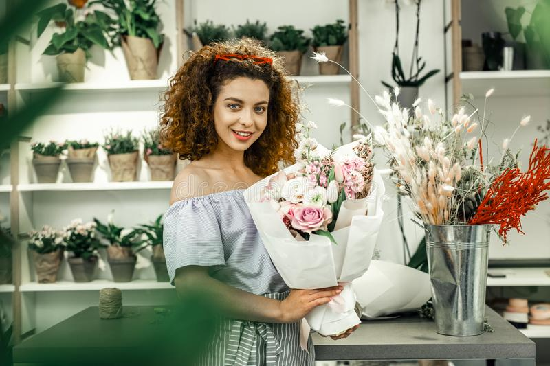Young promising florist feeling satisfied after making beautiful bouquet royalty free stock image