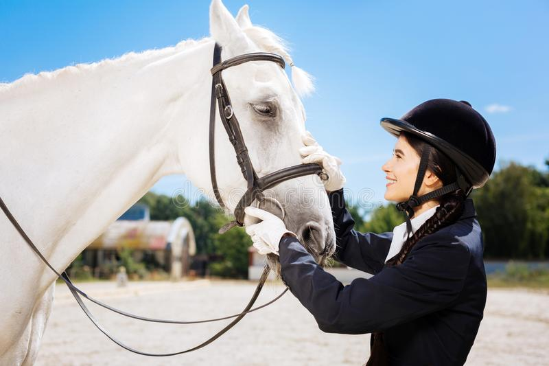 Young promising horsewoman coming to her lovely white horse. Promising horsewoman. Young promising horsewoman feeling excited while coming to her lovely white stock photos