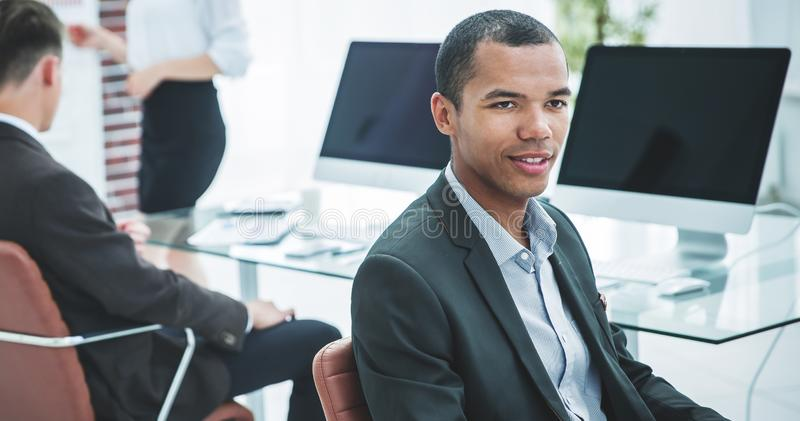 Promising young employee sitting behind a Desk royalty free stock photos