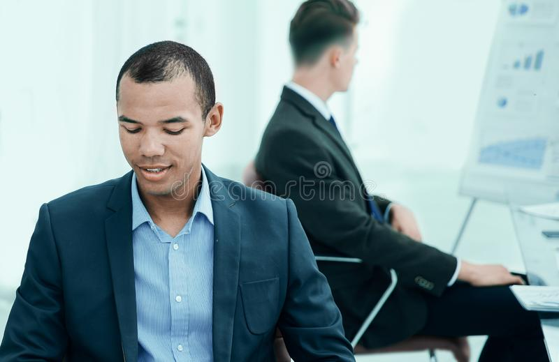 Promising young employee sitting behind a Desk stock photography