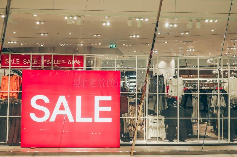 A promoção de vendas das mulheres forma a loja da roupa no shopping, etiqueta do sinal da etiqueta da venda na frente dos vidros  imagens de stock royalty free