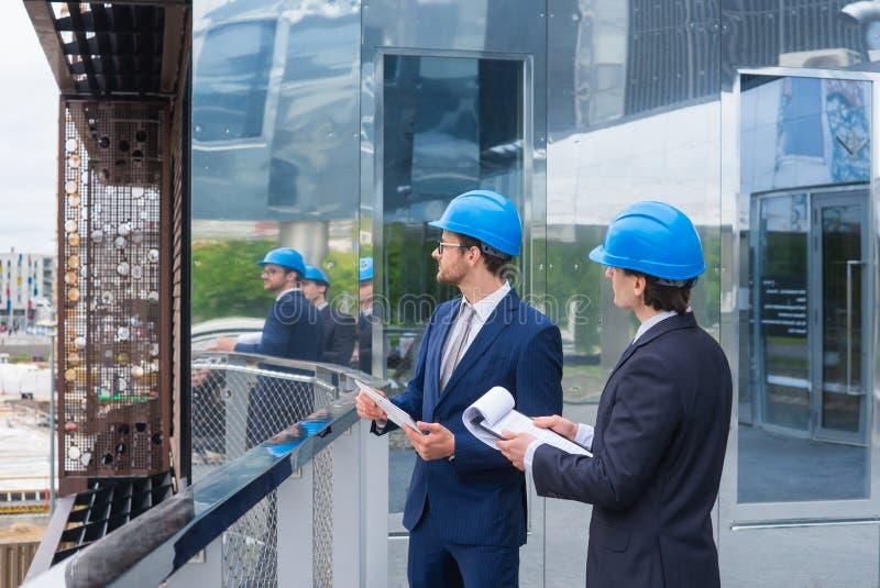 Promoteurs immobiliers dans les casques Construction neuve de bureau Hommes sûrs et architecte d'affaires parlant devant images libres de droits