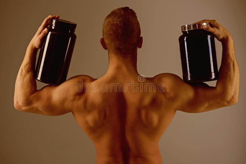 Promoting proper body functioning. Strong man hold supplement bottles. Eat a healthy diet. Muscular man with vitamin stock images