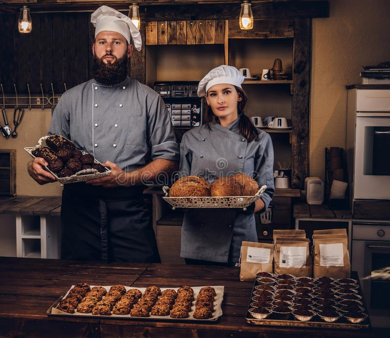 Chef with his assistant showing fresh bread in the kitchen. Promotion in bakery. stock photo