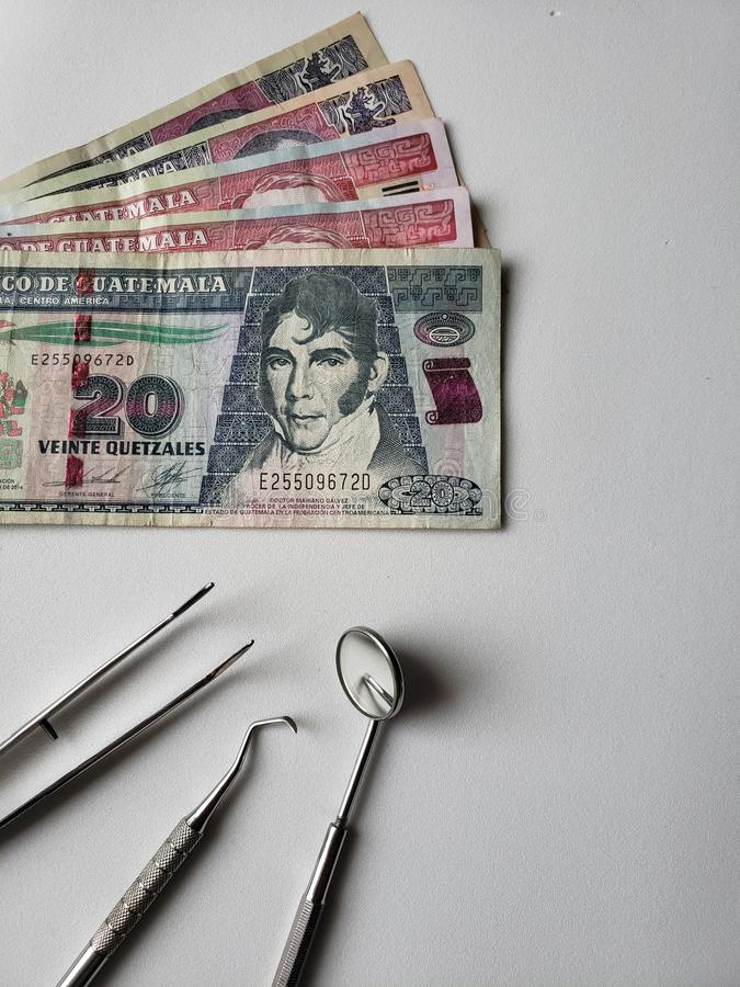 dentist utensils for oral review and guatemalan banknotes stock image