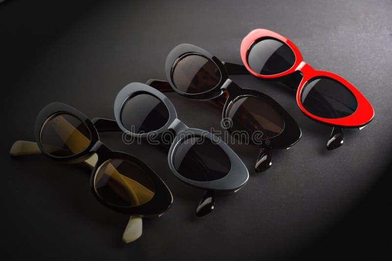 Promotion optique, affiche avec des lunettes de soleil dans diff?rentes couleurs sur le fond gris-fonc? images stock
