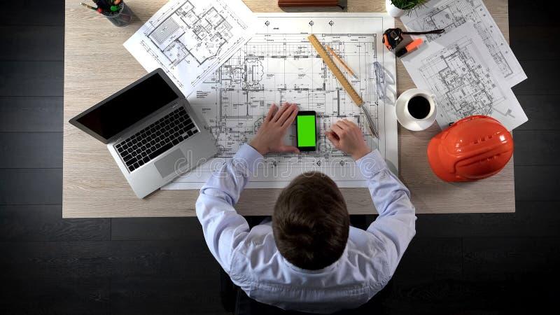 Promotor que comprueba la información sobre la construcción de la casa en el teléfono de pantalla verde imagen de archivo libre de regalías