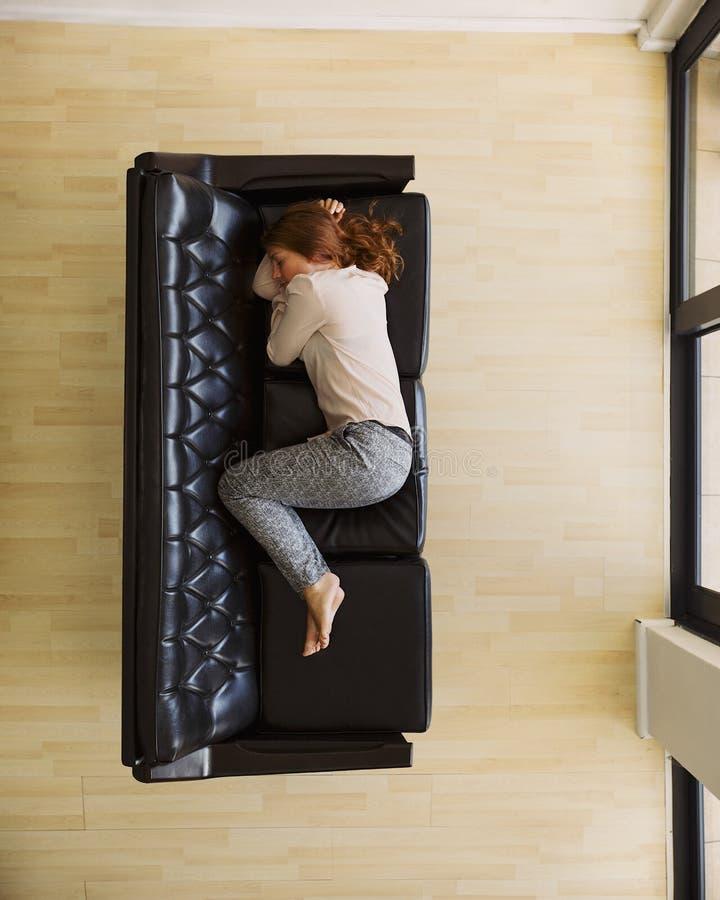 Propósito aéreo de dormir femenino joven en el sofá foto de archivo