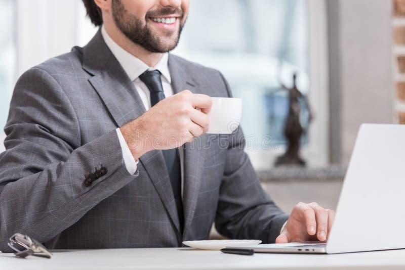 propósito cosechado del café de consumición sonriente y de mecanografiar del hombre de negocios en el teclado del ordenador portá fotografía de archivo