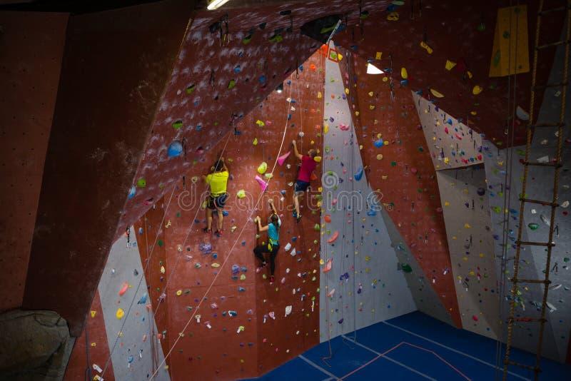 Propósito de la escalada del instructor y de los atletas en club de fitness imágenes de archivo libres de regalías
