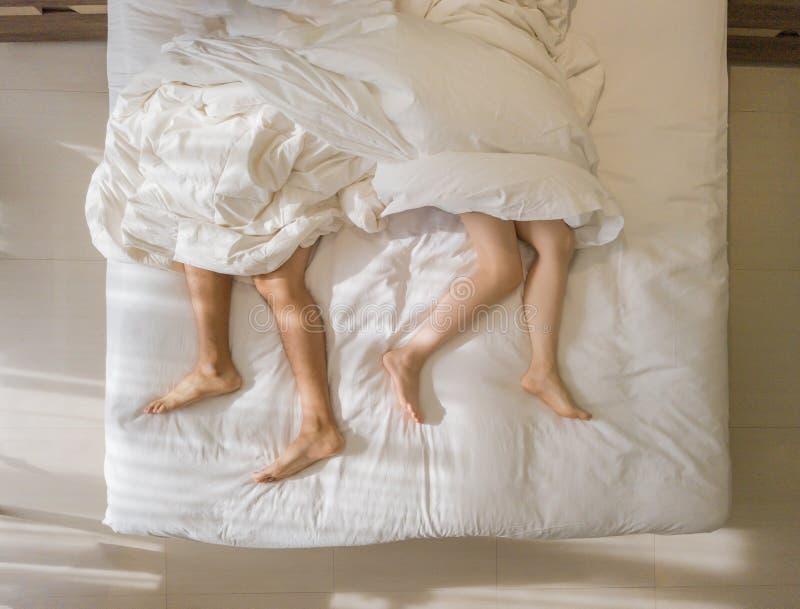 Propósito superior de dormir romántico de los pares pies desnudos de sus piernas que mienten en una cama con la manta blanca en c foto de archivo libre de regalías
