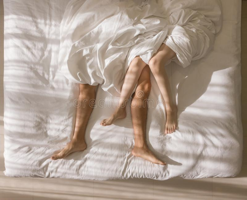Propósito superior de dormir romántico de los pares pies desnudos de sus piernas que mienten en una cama con la manta blanca en c fotografía de archivo