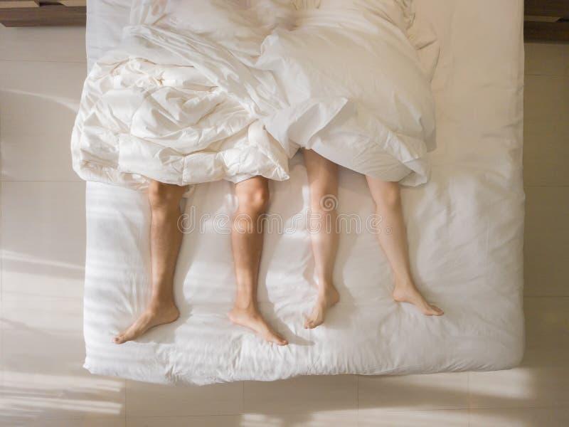 Propósito superior de dormir romántico de los pares pies desnudos de sus piernas que mienten en una cama con la manta blanca en c imagen de archivo libre de regalías