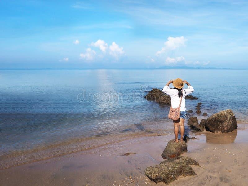 Prop?sito trasero de la situaci?n feliz de la mujer joven en la roca y de la mirada al oc?ano fotografía de archivo