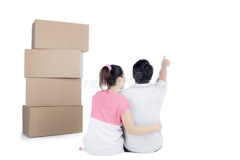 Propósito trasero de sentar pares lindos con la pila de cajas de cartón imágenes de archivo libres de regalías