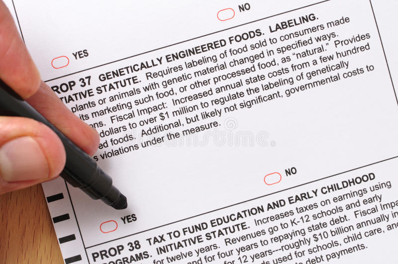 Prop 37 on ballot. Closeup of man about to mark vote for labeling genetically engineered foods on prop 37 ballot royalty free stock image