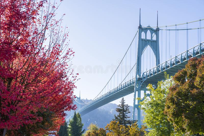 Prop Gothic St Johns Bridge in Portland in the colors of autumn. Popular gothic St Johns bridge with haze across the Willamette River in Portland industrial area stock image