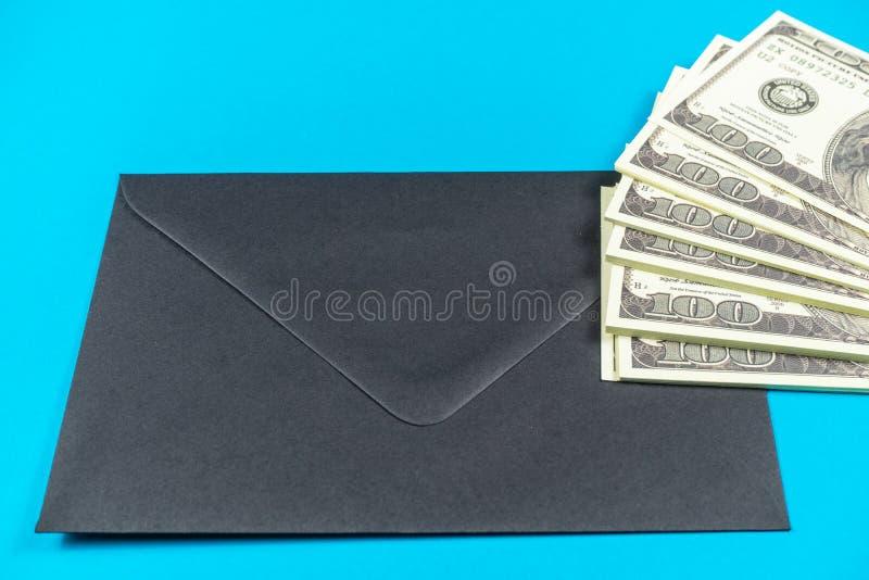 Prop Money Dollars and black envelope.Light blue background royalty free stock images