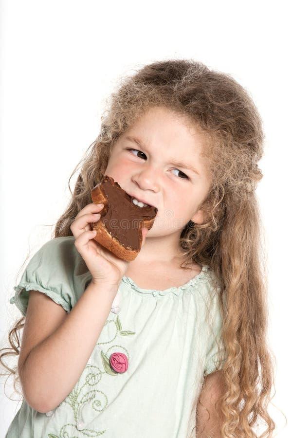 Propagação do chocolate comer do retrato da menina fotografia de stock
