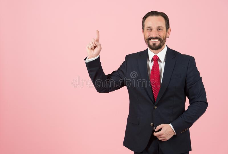 Propaganda pelo gerente de banco com dedo acima no espaço vazio O laço vermelho e o terno preto equipam pontos pelo dedo à propag fotografia de stock
