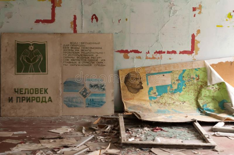 Propaganda posters with Lenin and other Bolshevik and communist leaders on floor near walls in abandoned school Pripyt. Ukraine, Pripyat, Chernobyl zone of royalty free stock photo