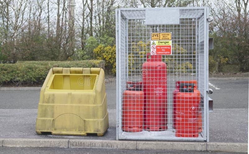 Propancylindrar för högt brännbar gas lagrar buren för säkerhet nära konstruktionsbyggnadsplats och det offentliga skyddet från e arkivfoton