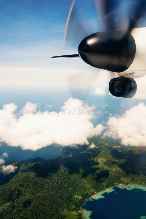Propeller aircraft wing over tropical island stock photography