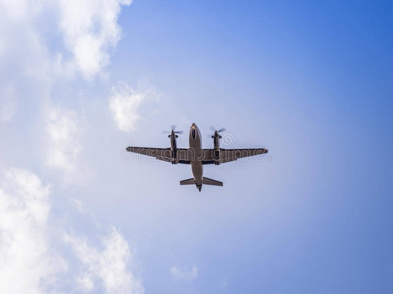 A propeller airplane sillhouette as it flies overhead. stock images