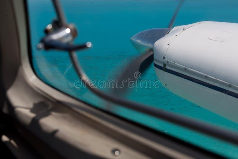 Propellern av ett litet flygplan över karibiskt vatten arkivfoto