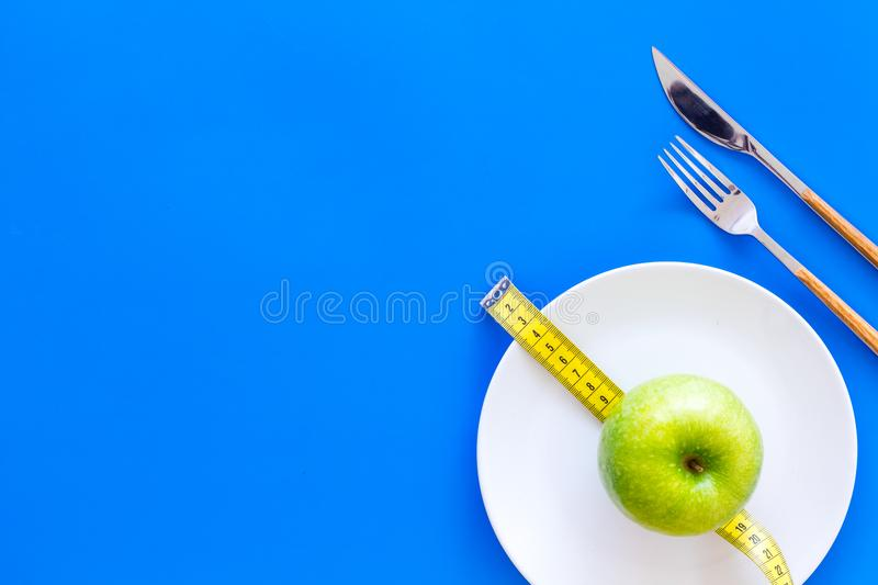 Proper nutrition with dietary fibre for weight loss. Apple on plate near measuring tape on blue background top view copy stock photo