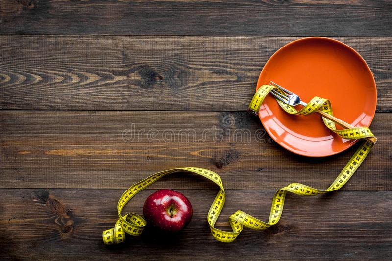 Proper nutrition for lose weight. Empty plate, apple and measuring tape on dark wooden background top view copy space. Proper nutrition for lose weight. Empty royalty free stock photo