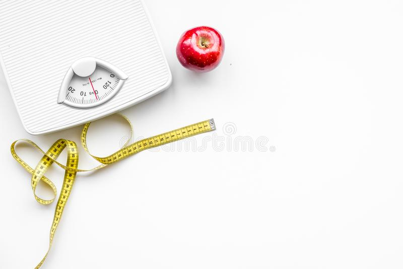 Proper nutrition for lose weight. Scale, measuring tape, apple on white background top view space for text.  stock photos