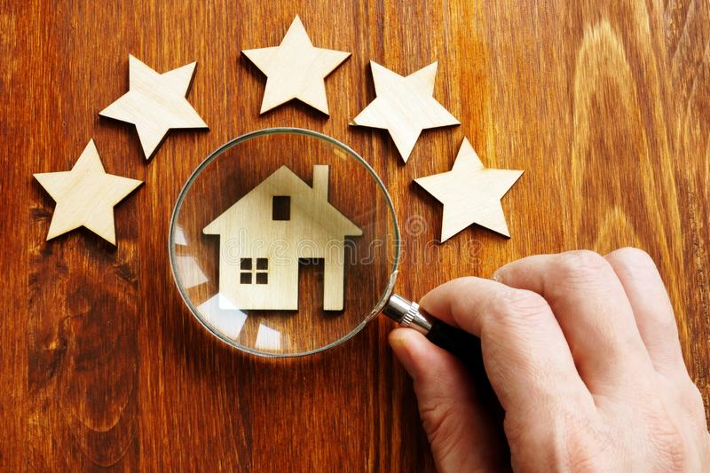 Property assessment concept. Hand holds magnifier, model of home and 5 stars stock image