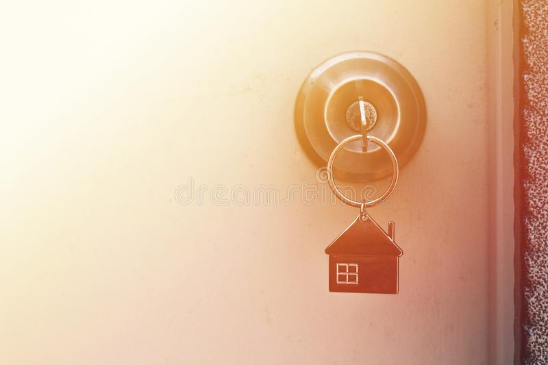 Property Concept, Home key with metal house keychain in keyhole royalty free stock photo