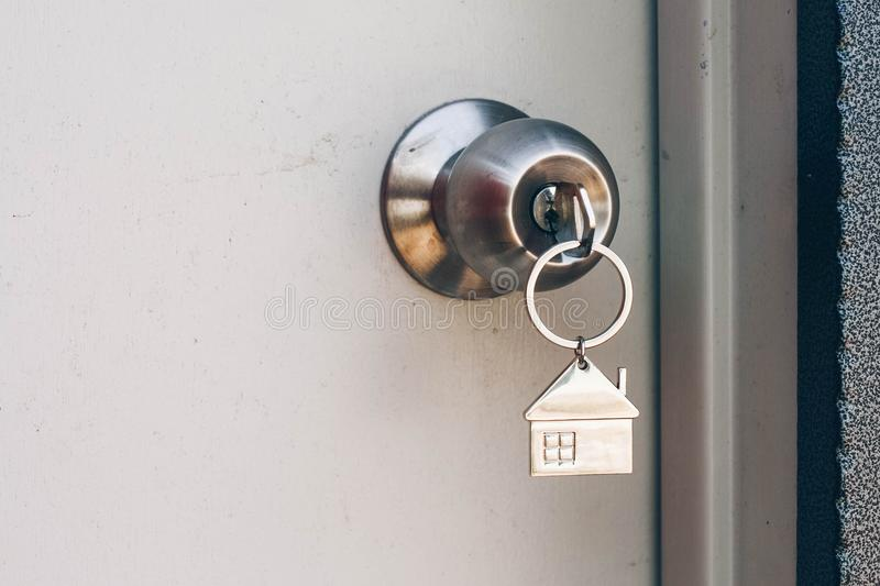 Property Concept, Home key with metal house keychain in keyhole stock photo