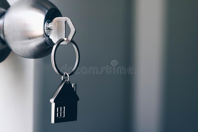 Property Concept, Home key with metal house keychain in keyhole.  royalty free stock photography
