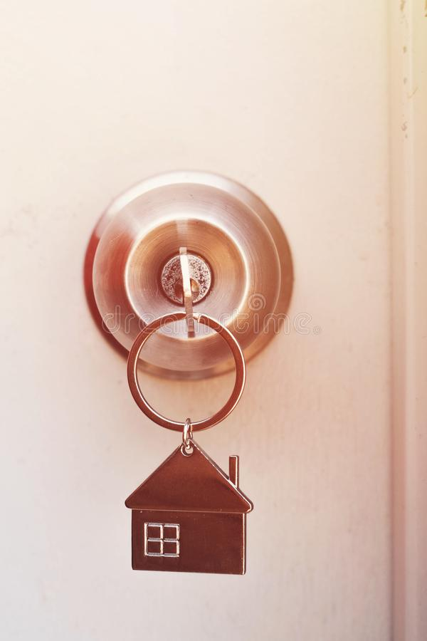 Property Concept, Home key with metal house keychain in keyhole royalty free stock images