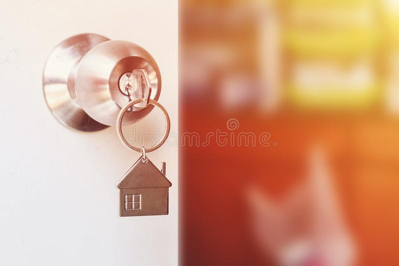 Property Concept, Home key with metal house keychain in keyhole royalty free stock image