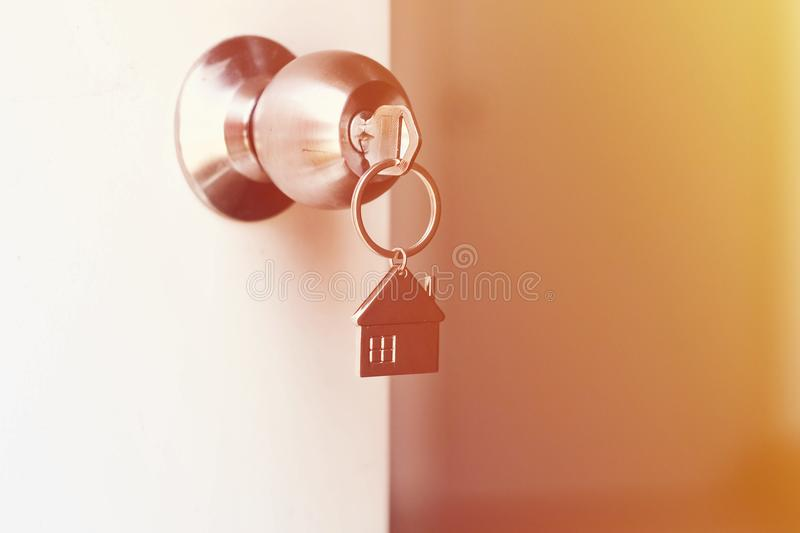 Property Concept, Home key with metal house keychain in keyhole.  stock image