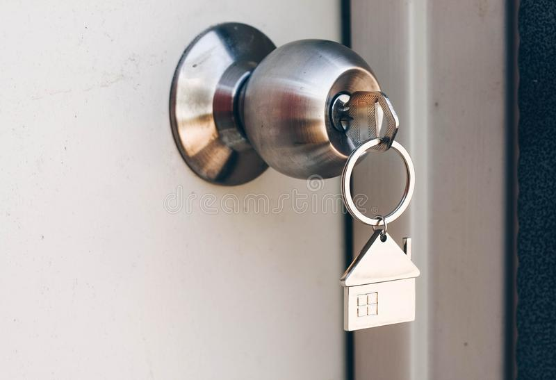 Property Concept, Home key with metal house keychain in keyhole royalty free stock photos